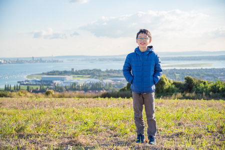Young asian boy standing on hill Stock Photo