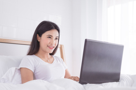 Beautiful asian woman using laptop computer on bed