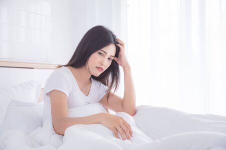 Asian woman having headache sitting on bed