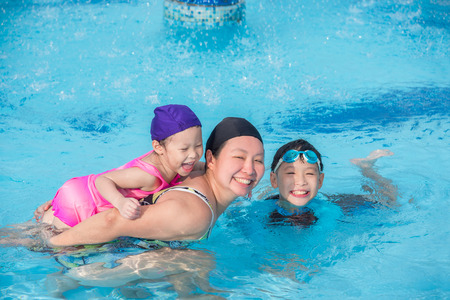 Asian mother and children in swimming pool Stock Photo