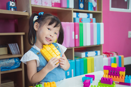 Little asian girl playing block at school