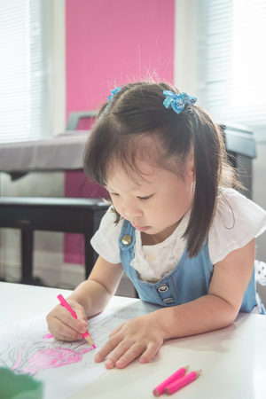little girl drawing picture at school