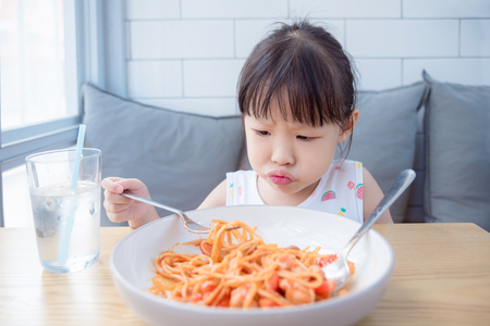 Little asian girl unhappy to have lunch