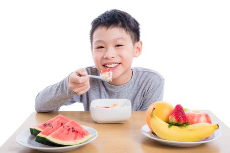 フルーツとヨーグルトを食べる少年 写真素材