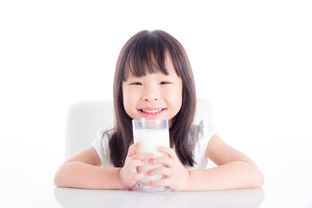Little asian girl sitting and holding a glass of milk over white background 스톡 콘텐츠