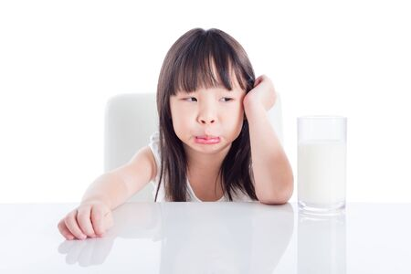 Little asian girl with unhappy face looking at a glass of milk isolated over white background Stock Photo