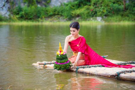 Beautiful Thai girl wearing red Thai traditional dress praying on river raft in Loy Krathong festival