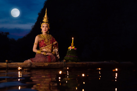 Beautiful asian girl in Thai traditional dress sitting on floating raft in Loy Krathong festival ,Thailand festival.