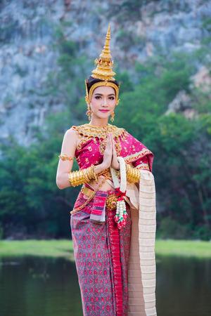 Schöne asiatische Frau im traditionellen thailändischen Kleid, das Gestenwillkommen tut und lächelt im Freien