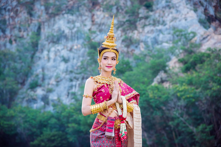 Beautiful asian woman wearing Thai ancient traditional costume holding flower ,standing near by the river and smiles