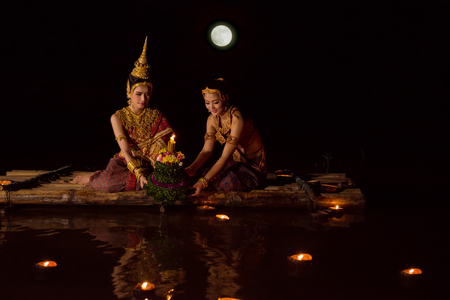 Beautiful asian women in traditional Thai dress floating krathong on floating raft in Loy Krathong festival ,Thailand festival.