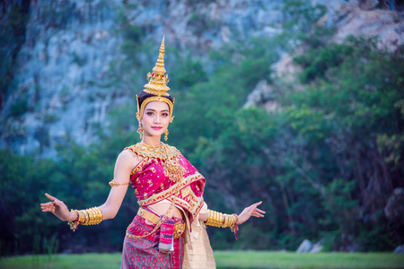 Beautiful asian woman wearing Thai ancient traditional costume dancing and smiles outdoor