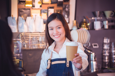 Beautiful asian barista giving coffee cup to her customer and smile at her cafe