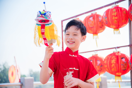Young chinese boy wearing traditional dreass and playing lion puppet in chinese new year festival Banque d'images