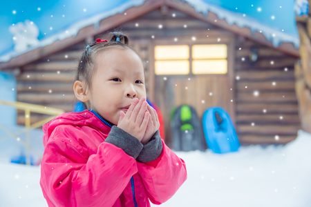 Little asian girl wearing pink jacket standing and blowing to warm up her hands outdoor when snow falling