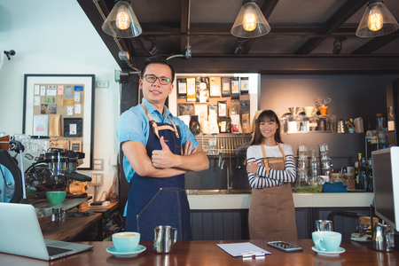 Asian barista in coffee shop Stock Photo