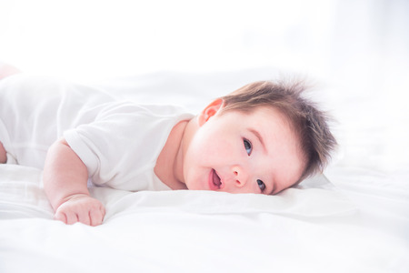 Little baby waking up on bed in the morning