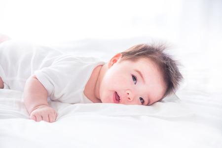 Pequeño bebé despertando en la cama por la mañana