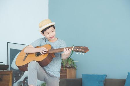 Young boy playing guitar at home Foto de archivo