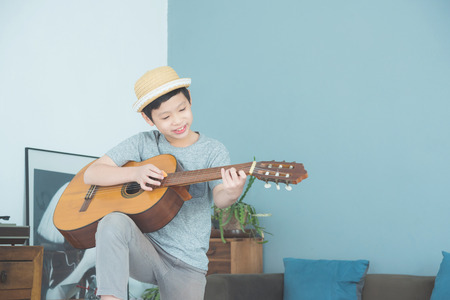 Young boy playing guitar at home Stock Photo