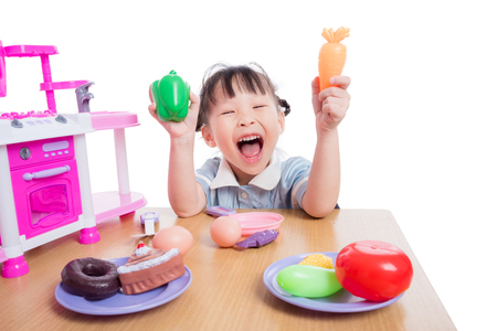 Girl playing kitchen toy on table