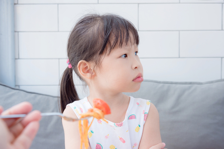 little girl refuse food from mother Stock Photo