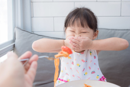 Little girl close her mouth by hands