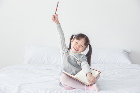 Little girl sitting on bed Stock Photo