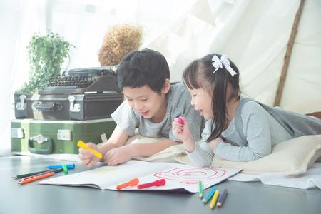 Siblings drawing on the floor
