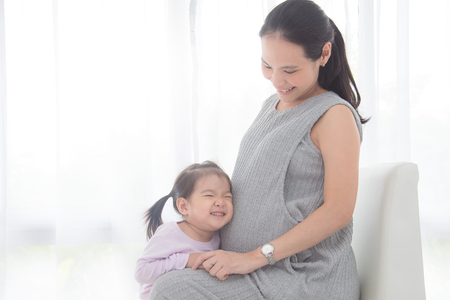 Little asian girl hugging her pregnant mother belly and smiles at home
