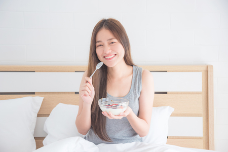 Beautiful young asian woman eating yogurt with berries for breakfast in the morning 스톡 콘텐츠