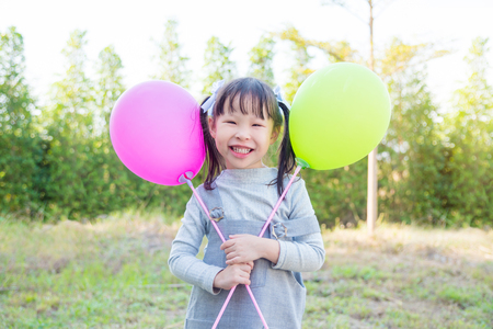 Little asian girl holding balloons and smiles in park