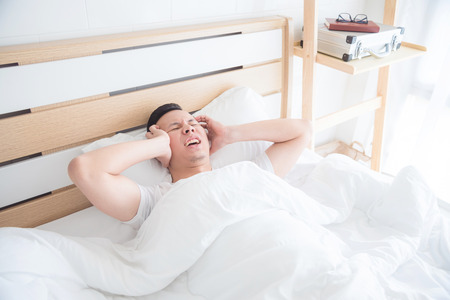Young man having headache on bed