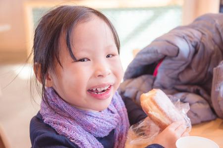 Little asian girl eating bread Stock Photo