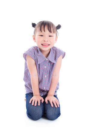 Little asian girl sitting on floor and smiles over white background