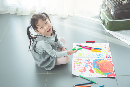 Little asian girl drawing picture by crayon