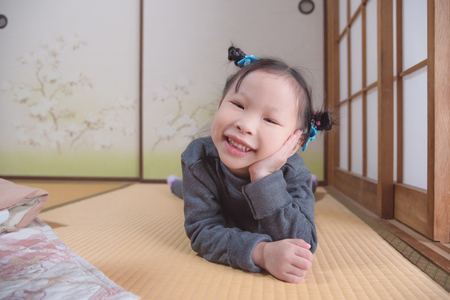 Little japanese girl lying on the floor and smile at camera