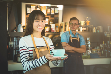 Beautiful asian barisata serving a cup of coffee to customer with smile
