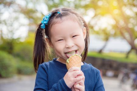 Little asian girl eating green tea icecream and smiles in park