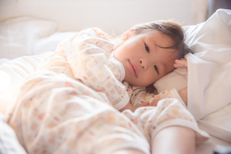 Little asian girl waking up on bed in early morning