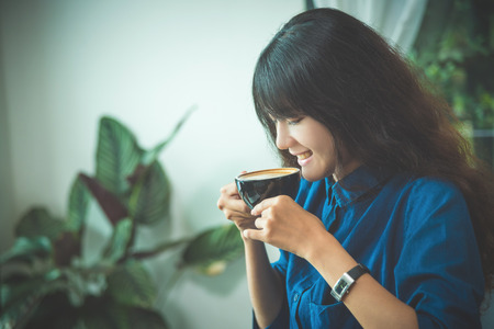 Beautiful young Asian woman drinking coffee and smile in coffee