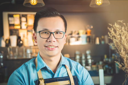Handsome Asian coffee shop owner smiling in his shop