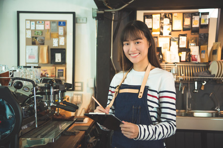 Beautiful asian barista smiling in coffee shop Stock Photo