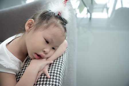 Sad asian girl sitting on sofa at home