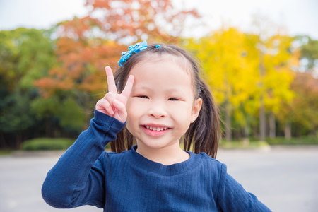 Little asian girl doing gesture victory hand with smiles in park