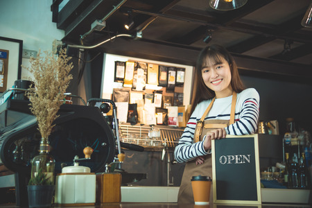Beautiful barista holding blackboard with wordopen and smiles Stock Photo