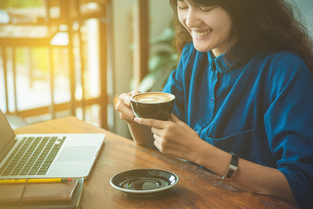 Beautiful young Asian woman drinking coffee and looking at laptop computer Stock Photo