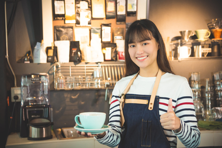 Beautiful asian barista holding coffee cup and showing thumb up with smiles