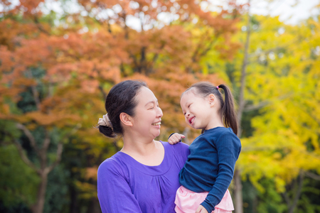 Asian woman holding her daughter and smiling together in autumn park