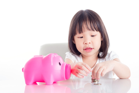 Little asian girl counting coin from pink piggy bank over white background